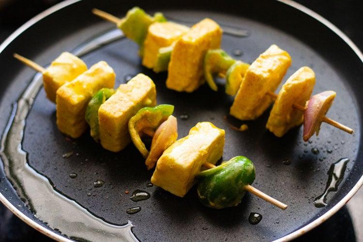 paneer tikka skewers being pan fried on a skillet