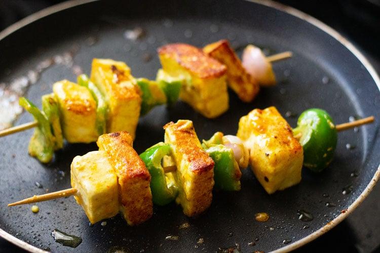 paneer tikka skewers being pan fried till golden