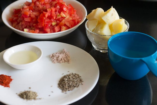 preparing aloo tamatar recipe