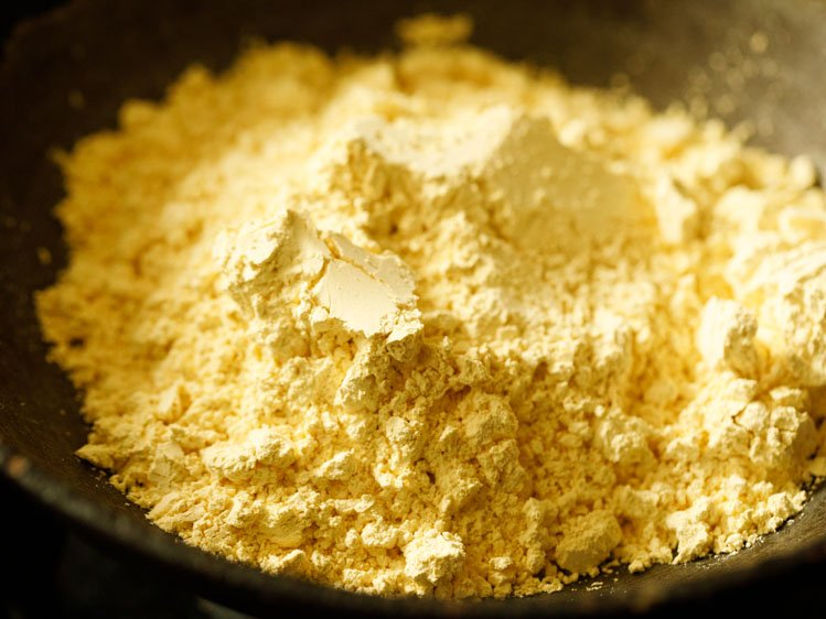 besan (gram flour) added in a heavy kadai or wok