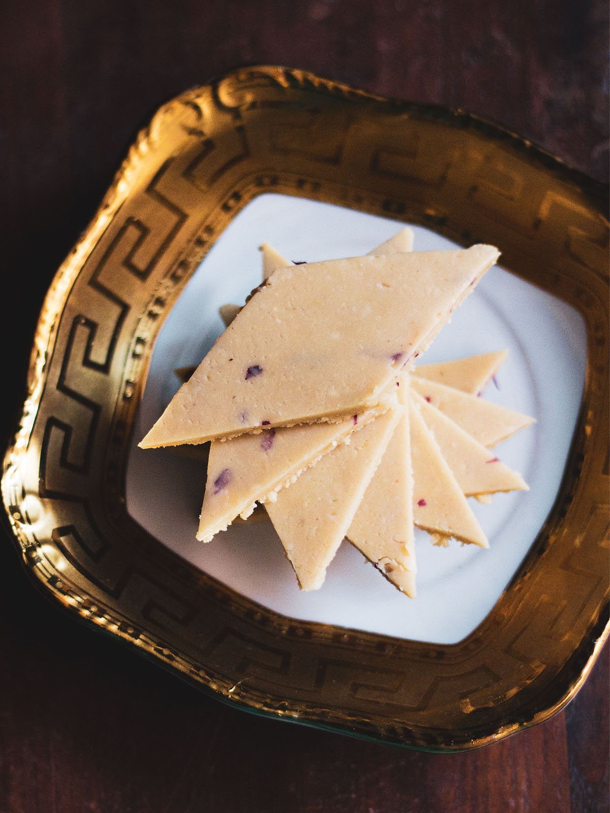kaju katli stacked spirally on a golden rimmed white square plate