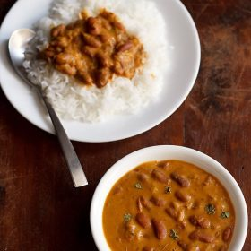 rajma masala garnished with a few kasuri methi and served in a white bowl on a brown wooden board and a plate of rice and rajma curry with a spoon kept on left top side of the board