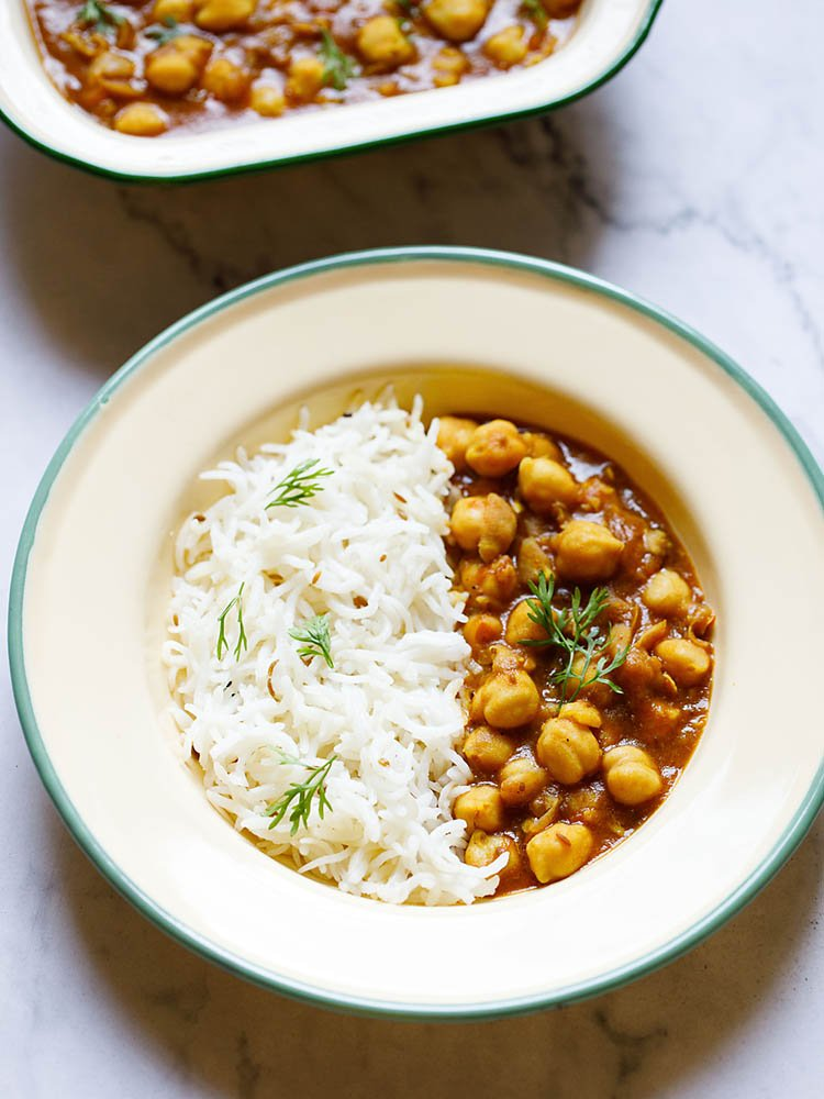 Instant Pot Chana Masala in a shallow plate with cumin rice by the side garnished with coriander sprigs