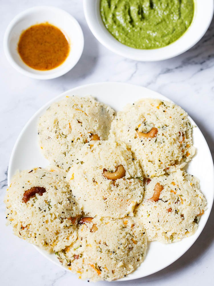 Rava Idli arranged in a circular way on a white plate kept on a white marble backdrop with two chutney (dips) placed above the plate.