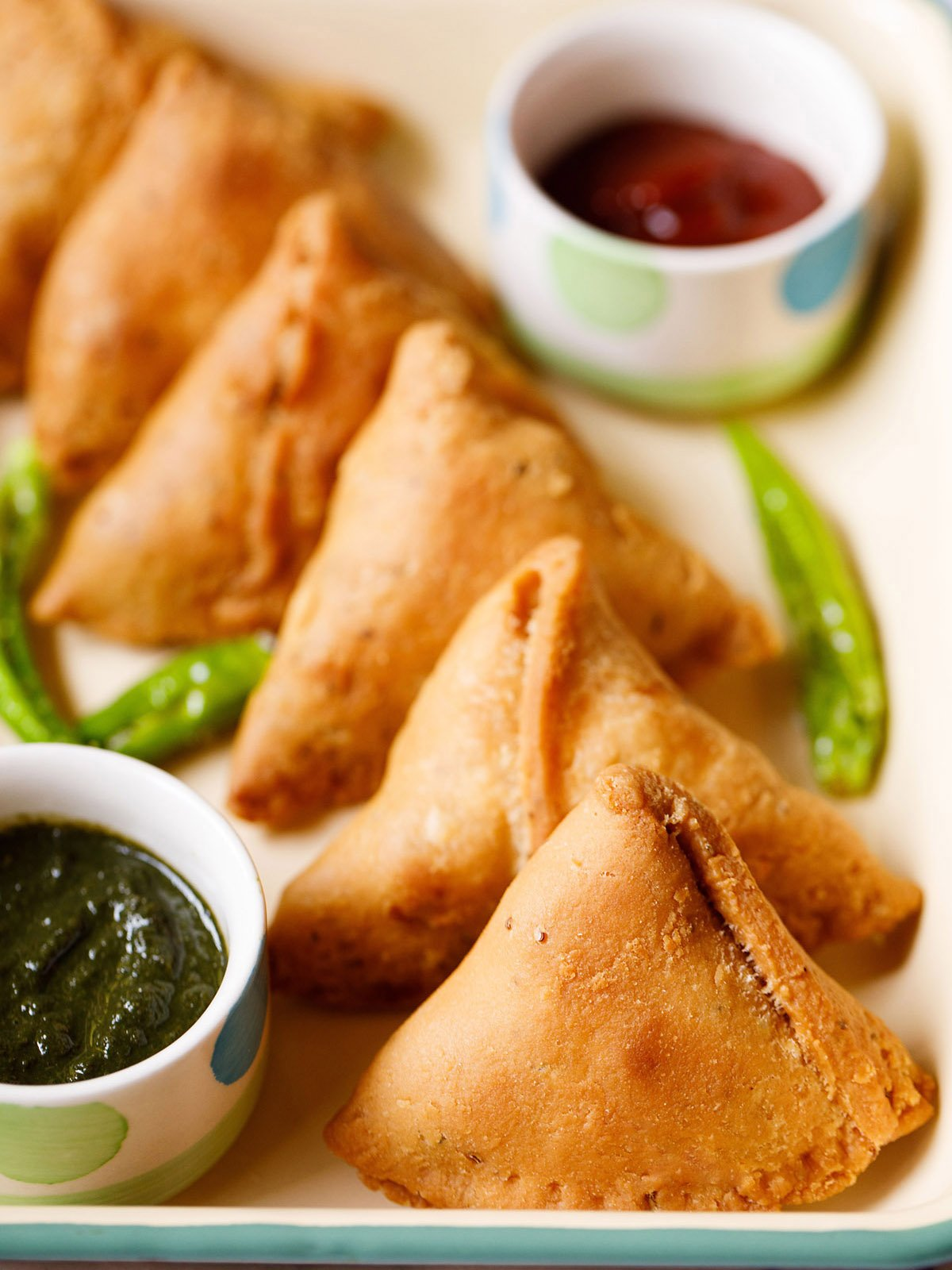 samosa stacked neatly on a cream tray with small bowls of chutney and salted fried green chillies