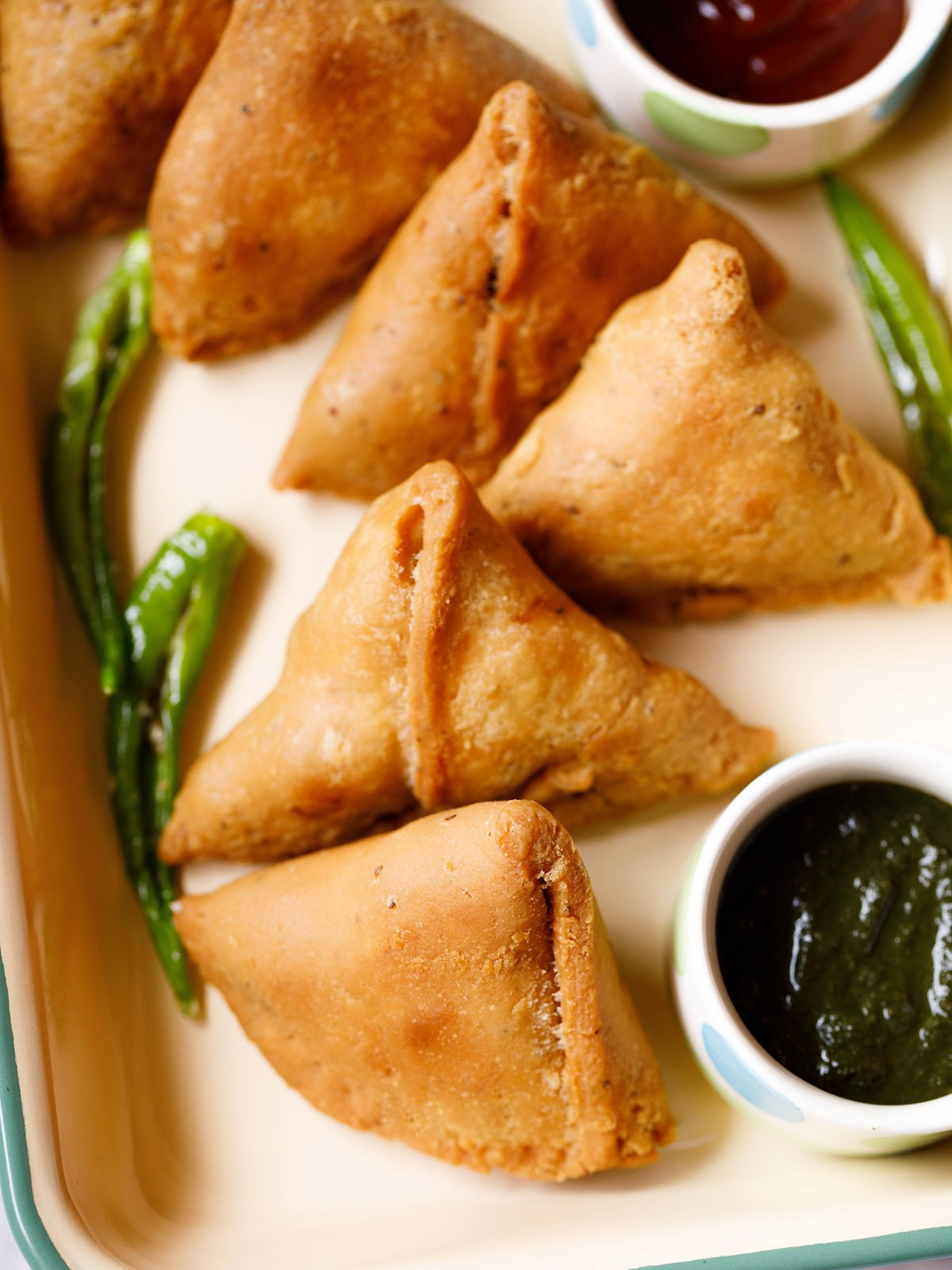 samosa kept in a tray with a bowl of green chutney and some salted fried green chillies