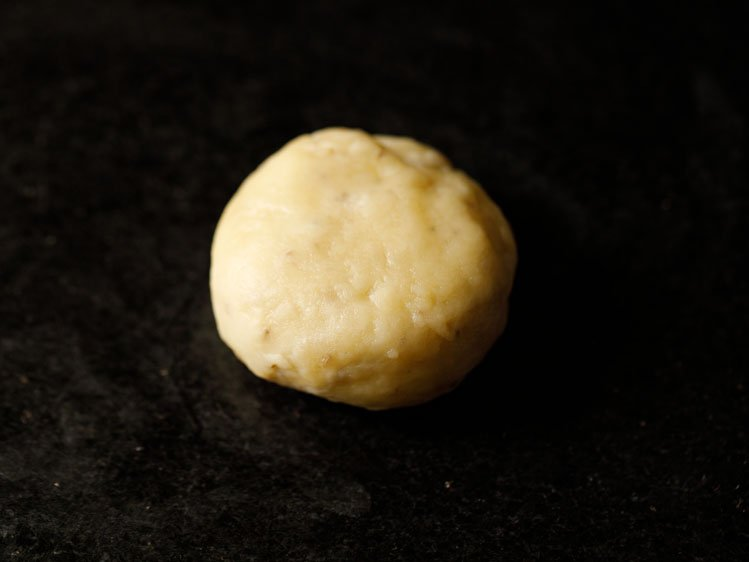 a dough ball flattened on a black surface