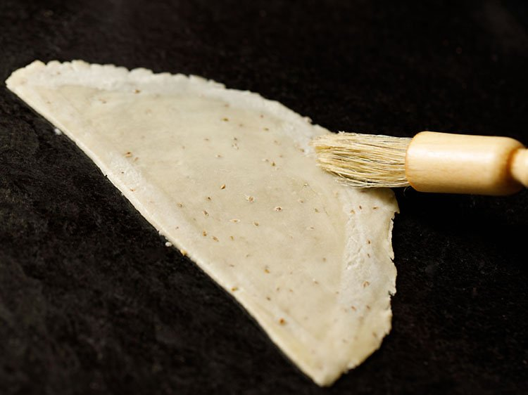 brushing with water with a pastry brush on the sides of the cut dough