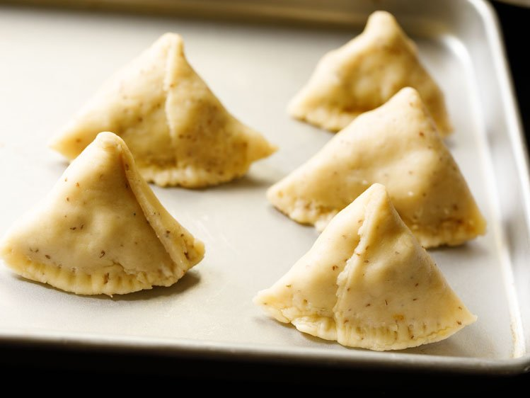 uncooked samosa shaped and kept on a silver tray