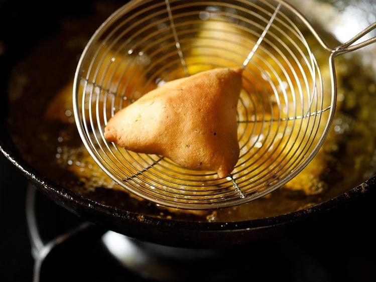 crispy fried samosa in a skimmer spoon