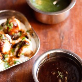 tamarind chutney garnished with one sprig of coriander served in a steel bowl with a square plate of Dahi Vada kept in the left center and green chutney kept in a steel bowl on top