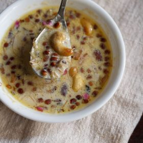 sheer khurma taken in a steel spoon on top of white bowl on a thick cream fabric