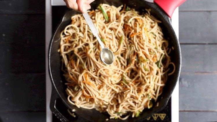 adding rice vinegar in veg noodles recipe