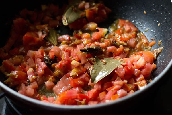 adding tomatoes to aloo gobi masala recipe