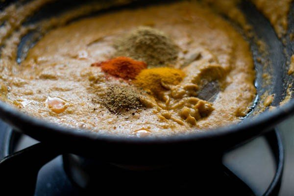 adding spices for making baby corn masala