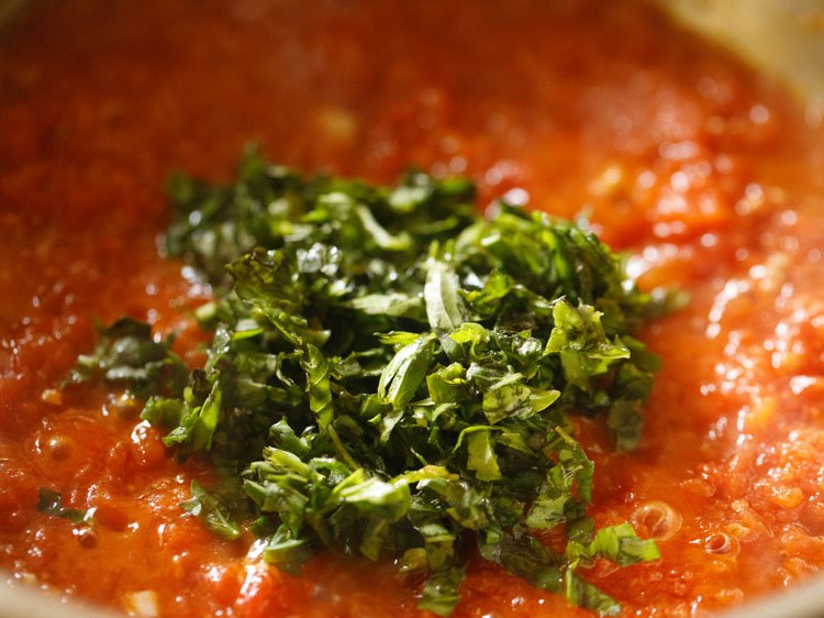 fresh basil added to pizza sauce