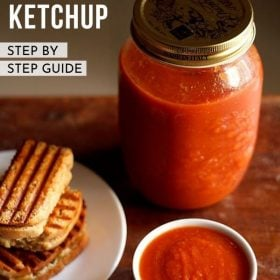 tomato ketchup served in white bowl next to a plate of grilled sandwiches and a mason jar of tomato sauce behind