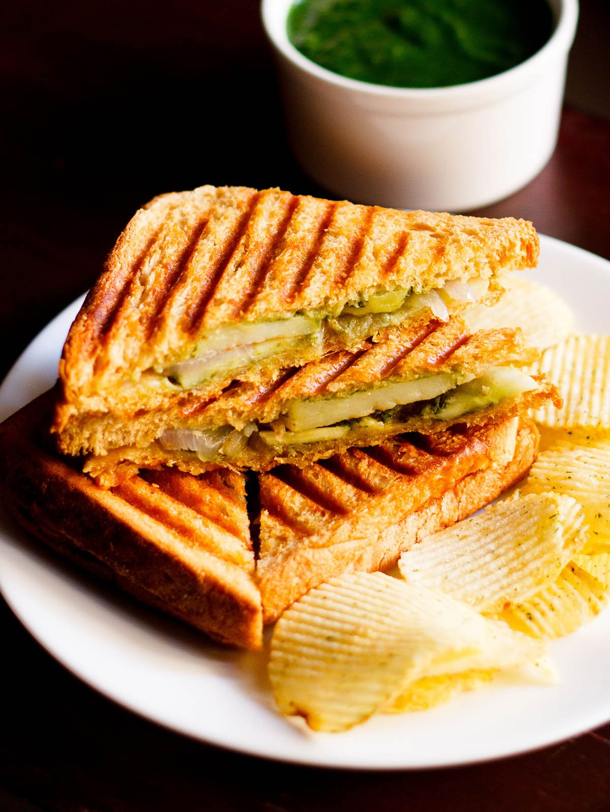 grilled sandwich with the filling side shown some potato wafers on a white plate