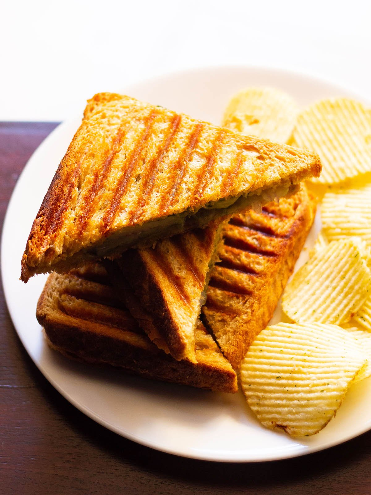 golden, crisp grilled sandwiches with a side of potato wafers on a white plate