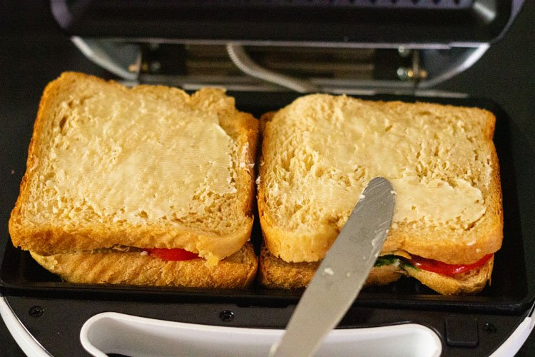 sandwich placed in a grill and butter being spread on top of bread slice