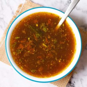 rasam served with a steel spoon in a blue rimmed white bowl placed on a jute mat