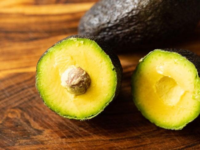 halve 2 medium-sized avocados on a board