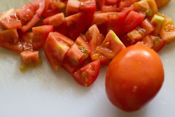 tomatoes on a white cutting board after being diced for making paneer makhani recipe