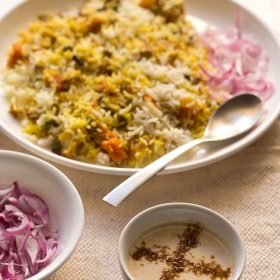 burani raita in a white bowl with vegetable biryani and some sliced red onions on a cream jute napkin