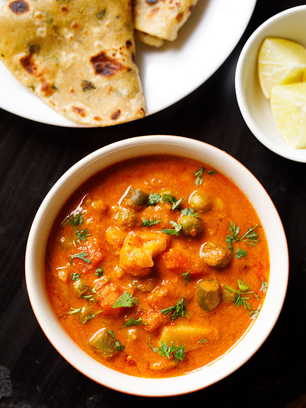 instant pot veg korma served in an off-white bowl with a plate of Indian flatbreads and a bowl of chopped lemons on a black slate board
