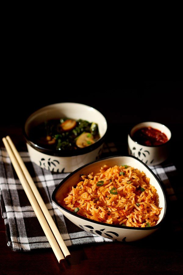 schezwan fried rice in a black and white triangular bowl with wooden chopsticks at the side