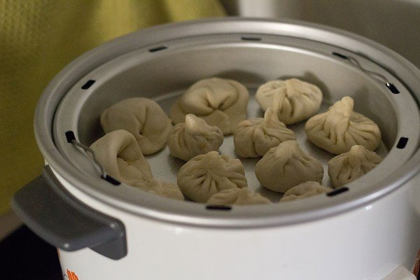 the steamer pan with the veg momos kept inside an electric cooker for steaming