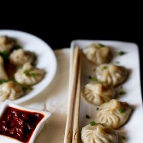 Veg momos arranged on a white rectangular long tray with a bamboo chopsticks by the side and a small square bowl of schezwan sauce at the side