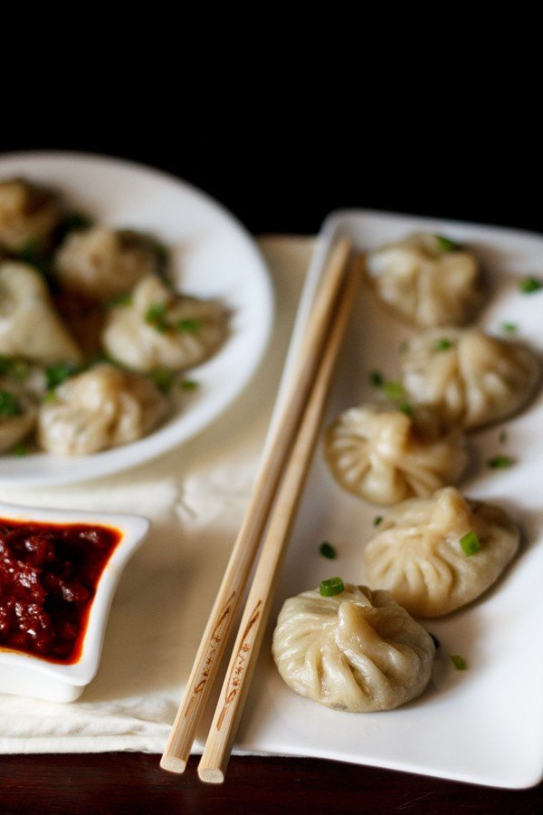 Veg momos arranged on a white rectangular long tray with a bamboo chopsticks by the side