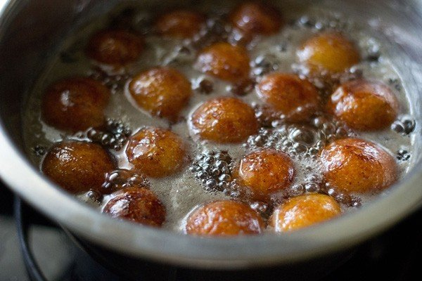 sugar syrup with gulab jamun being simmered