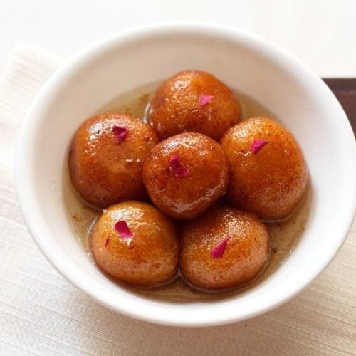 gulab jamun served in a white bowl