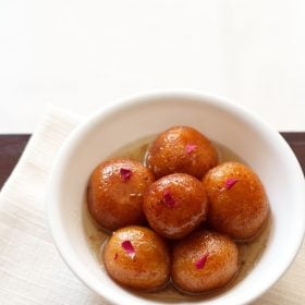 gulab jamun served in a white bowl on a white napkin