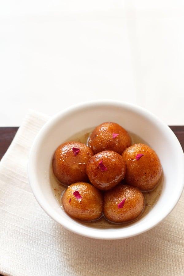 gulab jamun served in a white bowl on a white napkin
