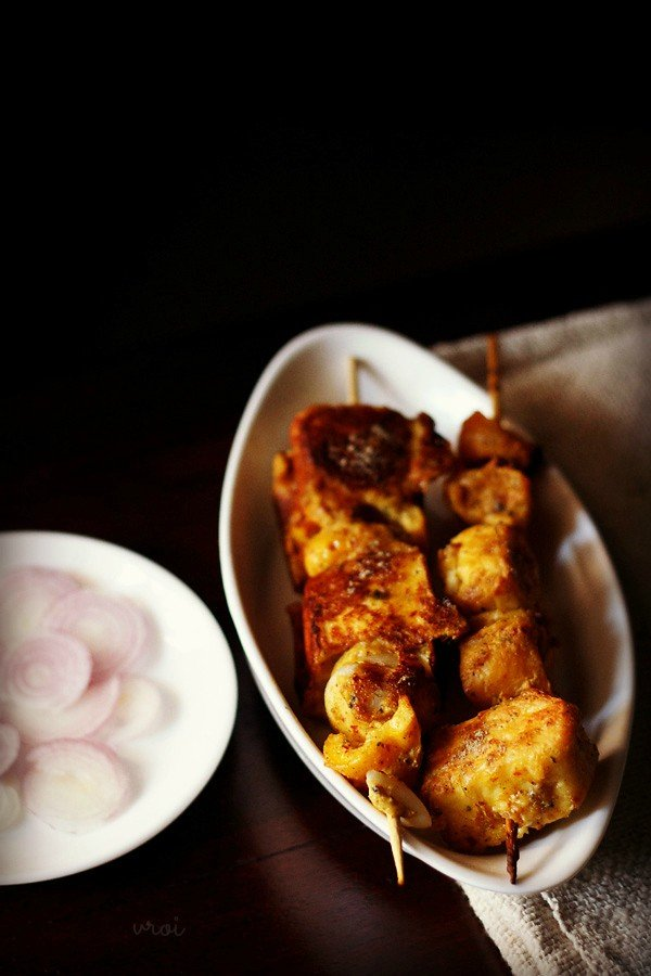 achari paneer tikka served in a white plate with onions