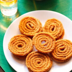 chakli served in a circle with a center chakli on a white plate with a green background