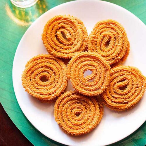 chakli kept on a white plate on a green background