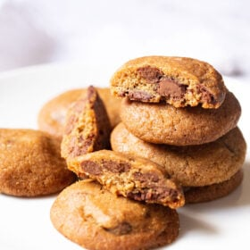 eggless chocolate chip cookies stacked with some halved cookies on a white plate