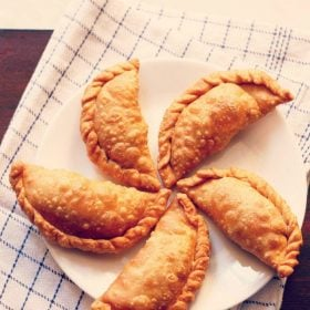 gujiya arranged neatly on a white plate placed on a white and blue checkered napkin p