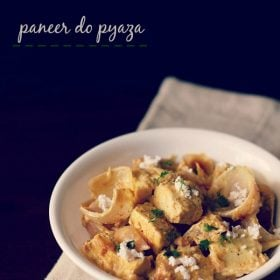 paneer do pyaza garnished with grated paneer and coriander leaves in a white bowl on a light beige napkin on a dark brown board