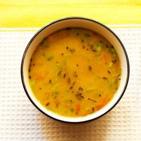 Gujarati dal in a black rimmed bowl on a white and yellow linen napkin