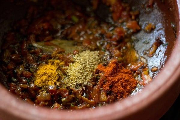 adding spice powders to make vegetable handi recipe