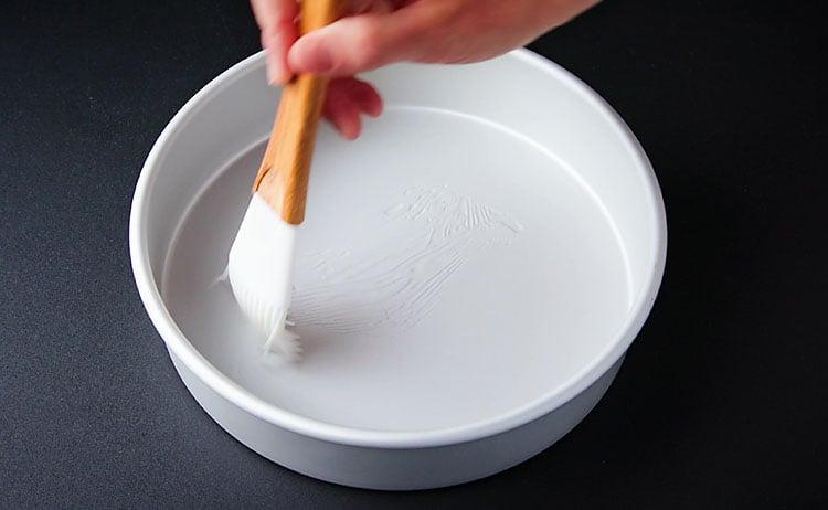 brushing cake pan with oil