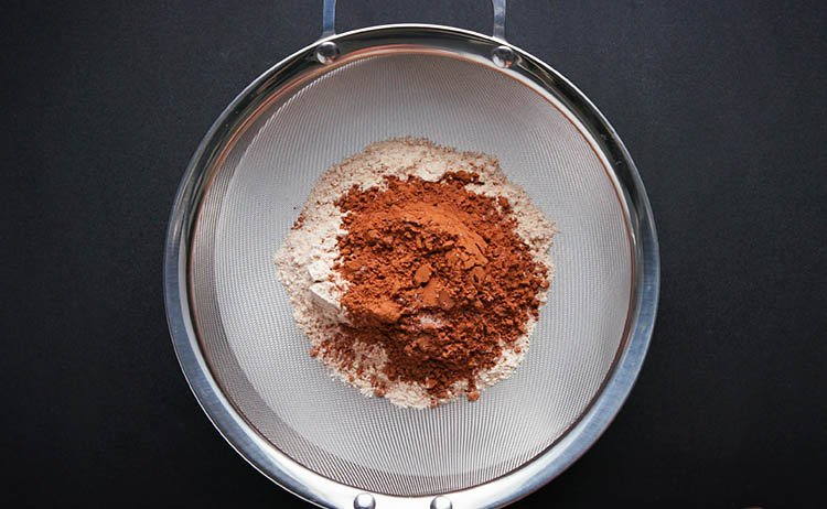 whole wheat flour and cocoa powder placed in a sieve for sifting