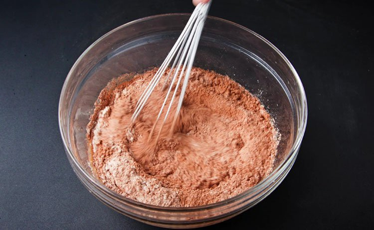 mixing eggless chocolate cake batter with a whisk