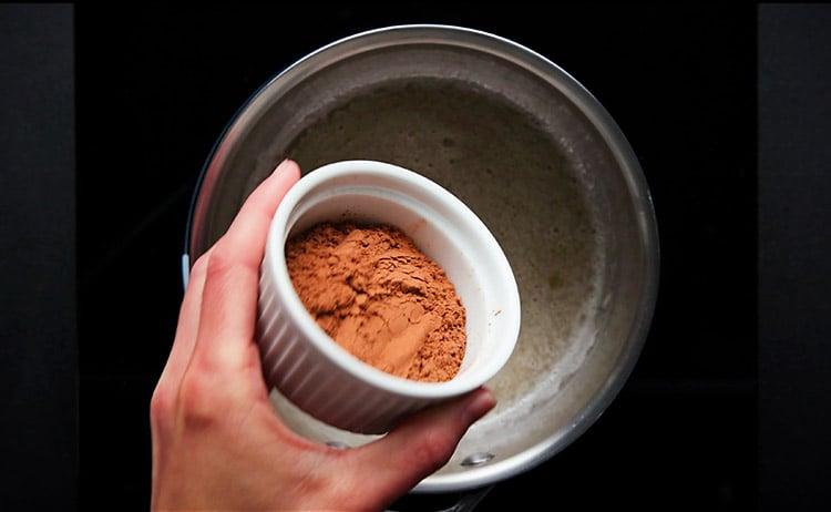 adding cocoa powder to almond milk mixture