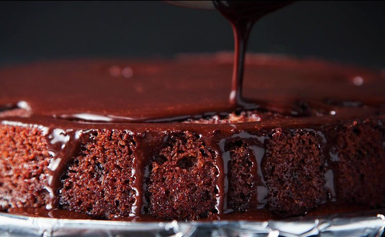 pouring the icing on the vegan chocolate cake